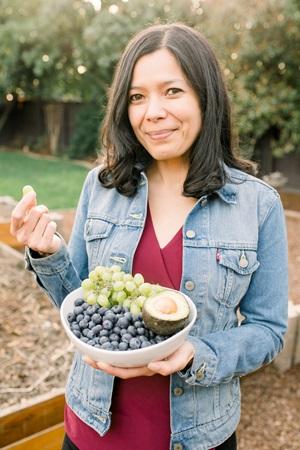 Toni Okamoto holding a plate of fruit